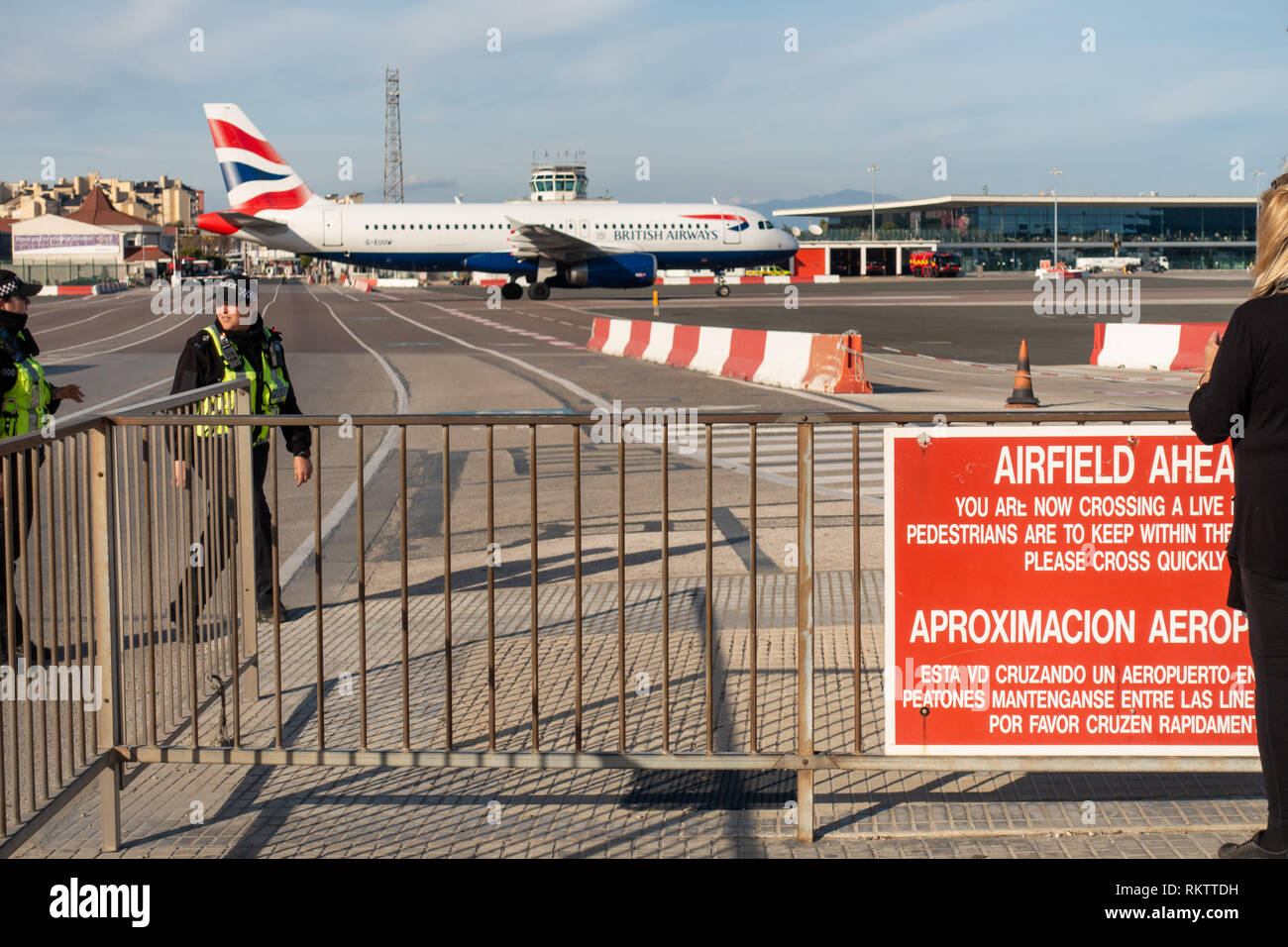 a British Airways Airbus A320 crosses the runway while traffic and pedestrians wait, at the famous airport crossing in Gibraltar Stock Photo