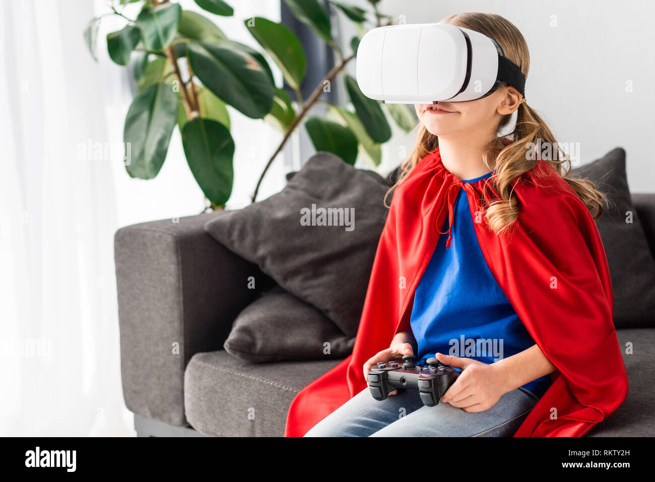 82465624fac Cute kid in red cloak and virtual reality headset playing video game - Stock  Image
