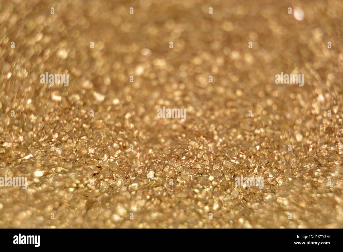 golden shimmer glitter texture with copy space, defocused golden glitter background with bokeh effects - Stock Image