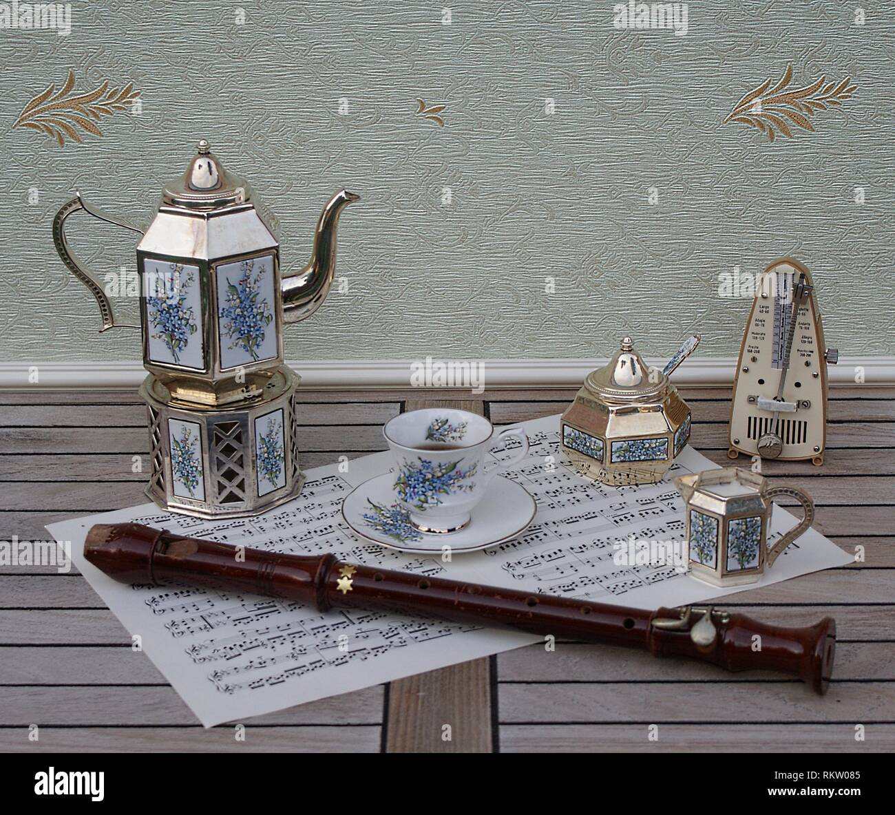 English teacup, silver-plated teapot, a stove, cream jug, sugar bowl and sugar spoon and metronome for music and a block flute on a sheet of music - Stock Image
