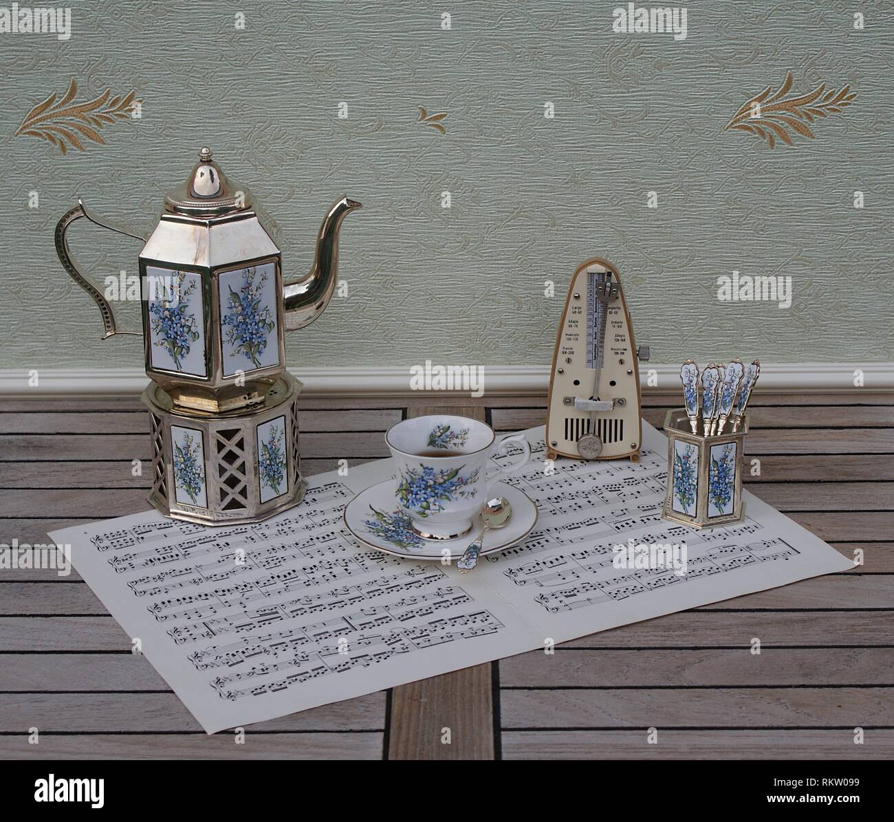 English teacup and saucer, silver-plated teapot on a silver stove, spoon vase and teaspoon and metronome for music on a sheet of music - Stock Image