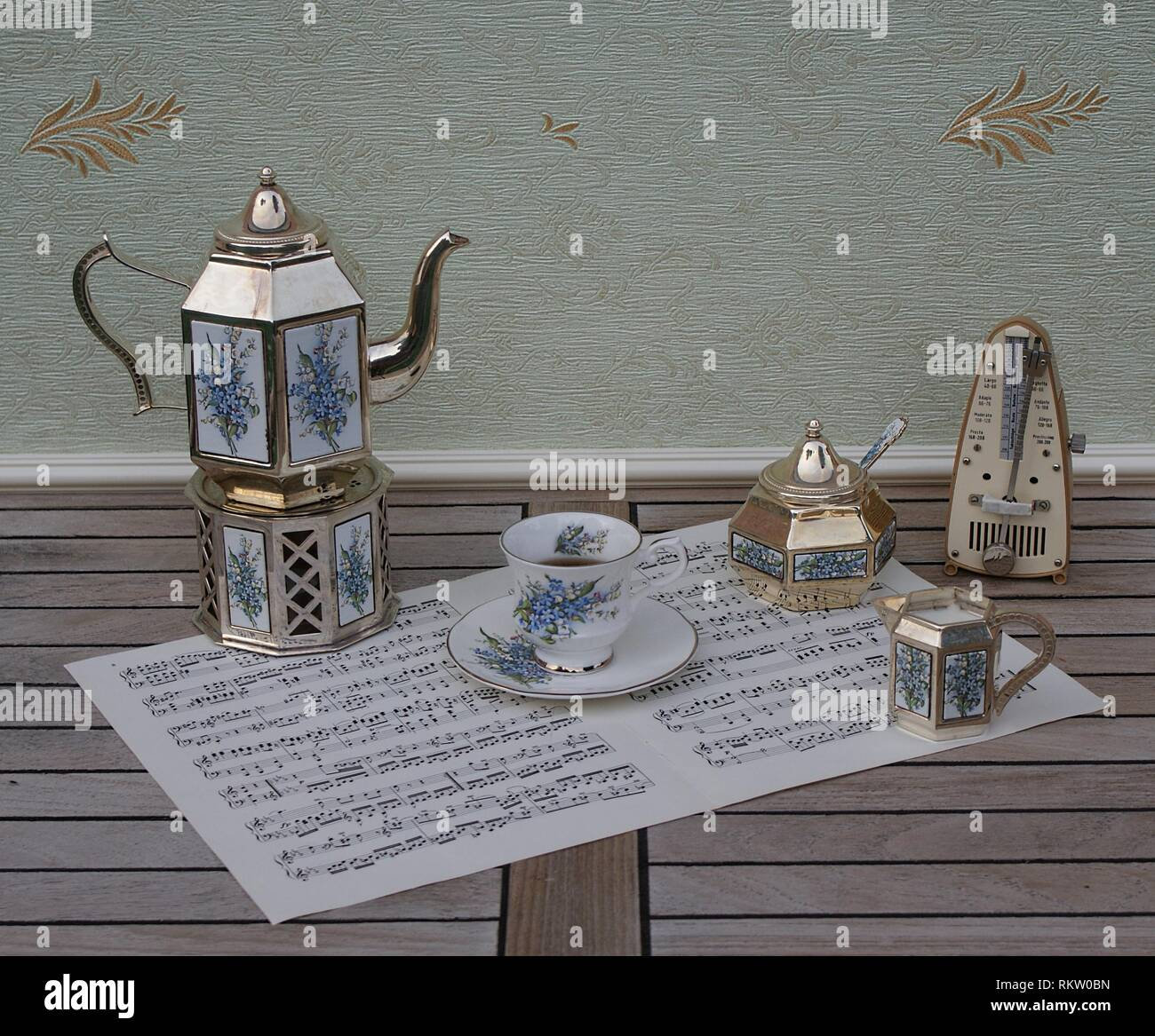 English teacup, saucer, silver-plated teapot on a silver stove, cream jug, sugar bowl and sugar spoon and metronome for music on a sheet of music - Stock Image