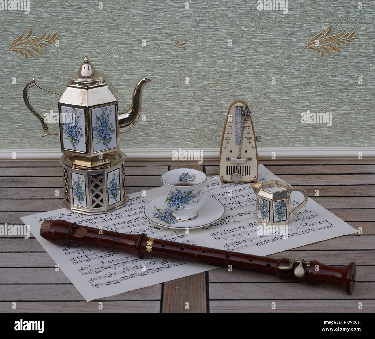 English teacup, saucer, silver-plated teapot on a silver stove, cream jug with floral decor, metronome for music and a block flute on a sheet of music - Stock Image