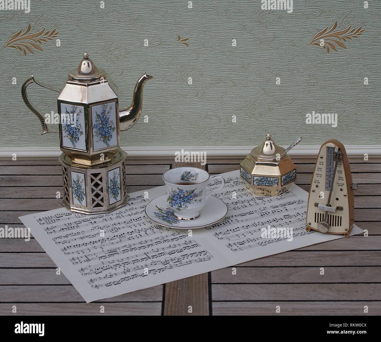 English teacup, saucer, silver-plated teapot on a silver stove, sugar bowl and sugar spoon and metronome for music on a sheet of music - Stock Image