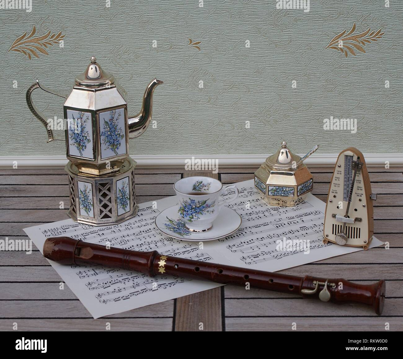 English teacup, saucer, silver-plated teapot on a silver stove, sugar bowl and sugar spoon, metronome for music and a block flute on a sheet of music - Stock Image