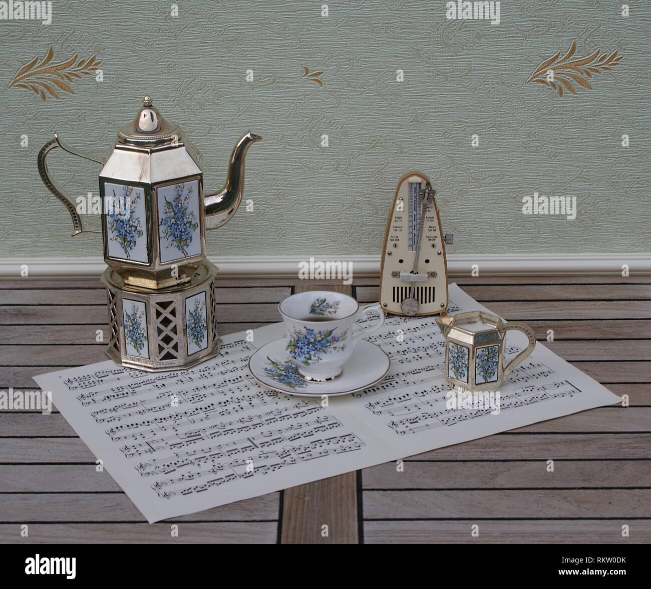 English teacup and saucer, silver-plated teapot on a silver stove, cream jug with floral decor, and metronome for music on a sheet of music - Stock Image