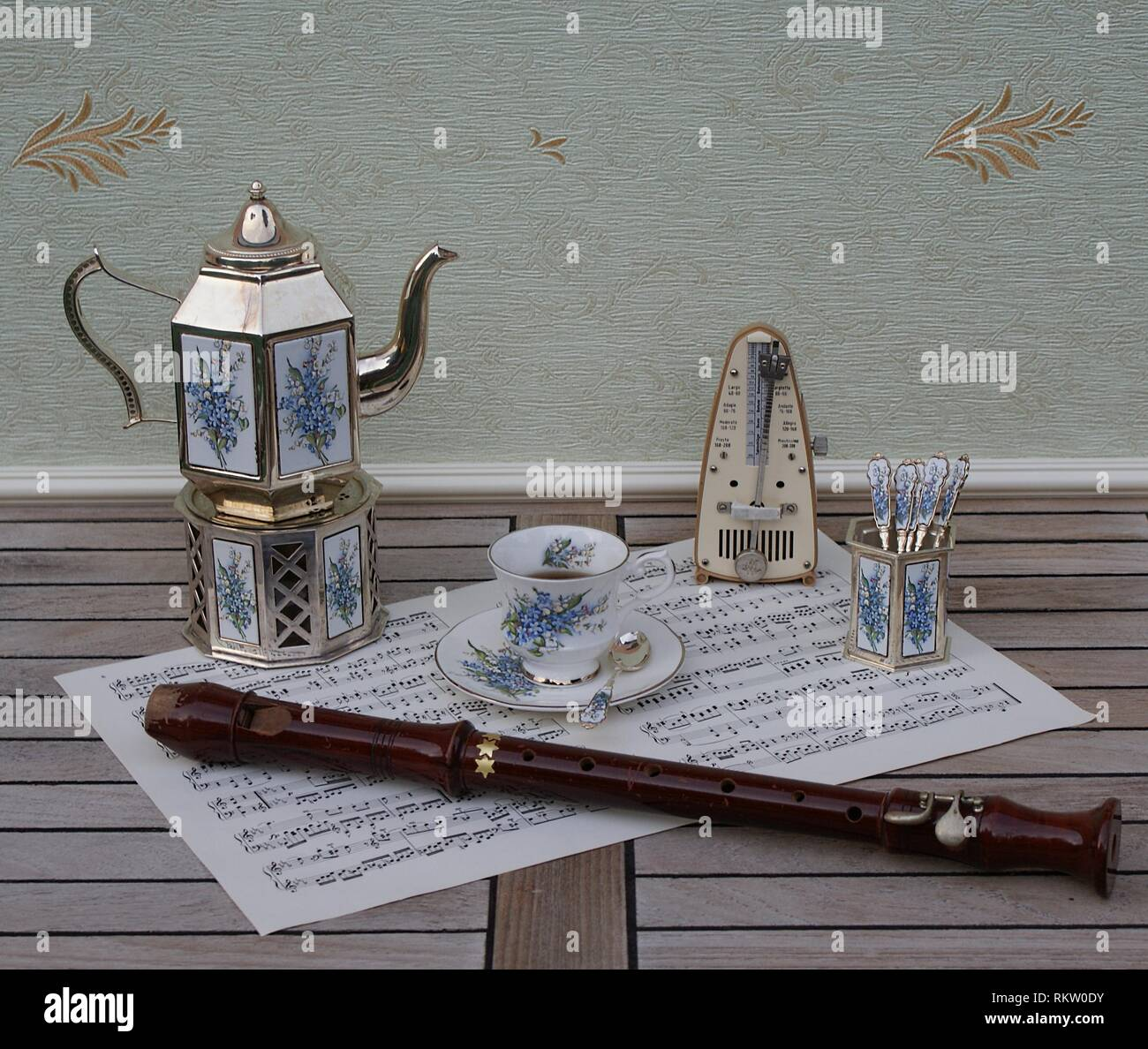 English teacup, saucer, silver-plated teapot on a silver stove, spoon vase and teaspoon and metronome for music and a block flut on a sheet of music - Stock Image