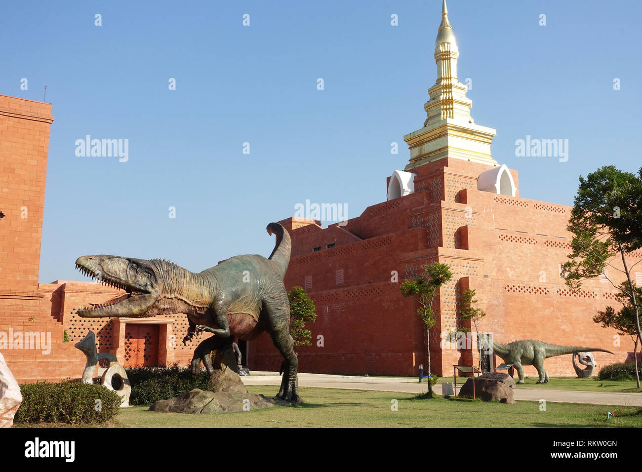 Dinosaur models outside the Bhodhidart relics pagoda Sukhothai airport Thailand - Stock Image