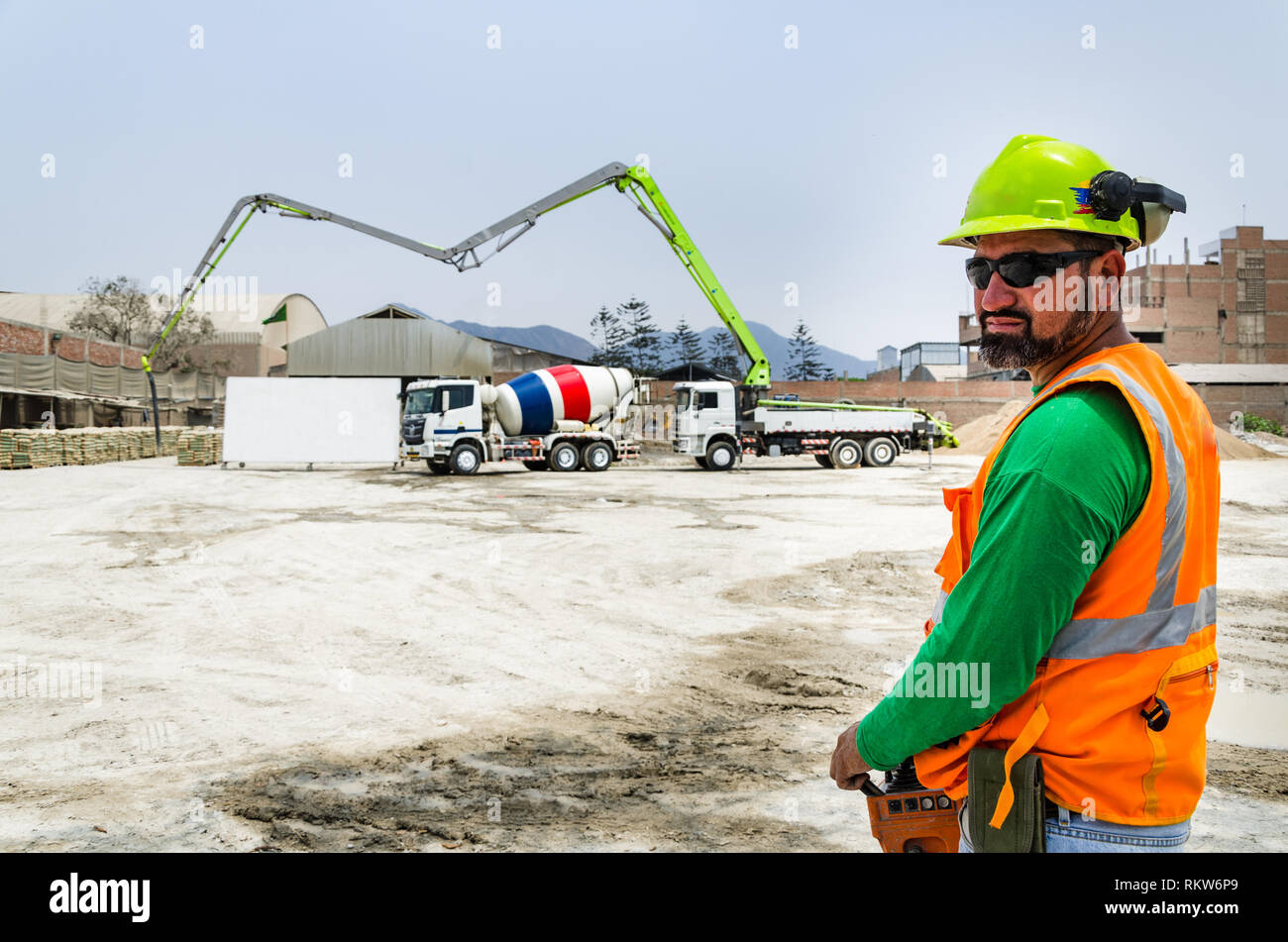 Concrete pump operator with remote control for boom pump truck at construction site. Stock Photo