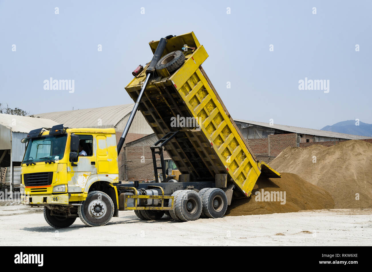 Ten yard dump truck delivering a load of dirt for a fill project at a new commercial development construction project - Stock Image