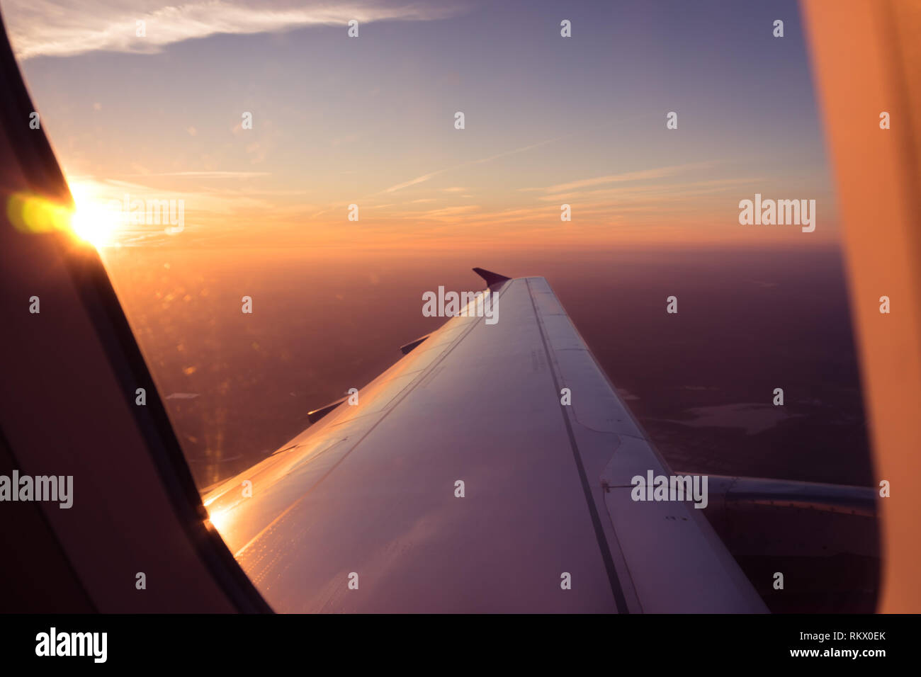 Passenger POV View Through Airplane Window, Sunrise Above The Clouds Aerial Stock Photo