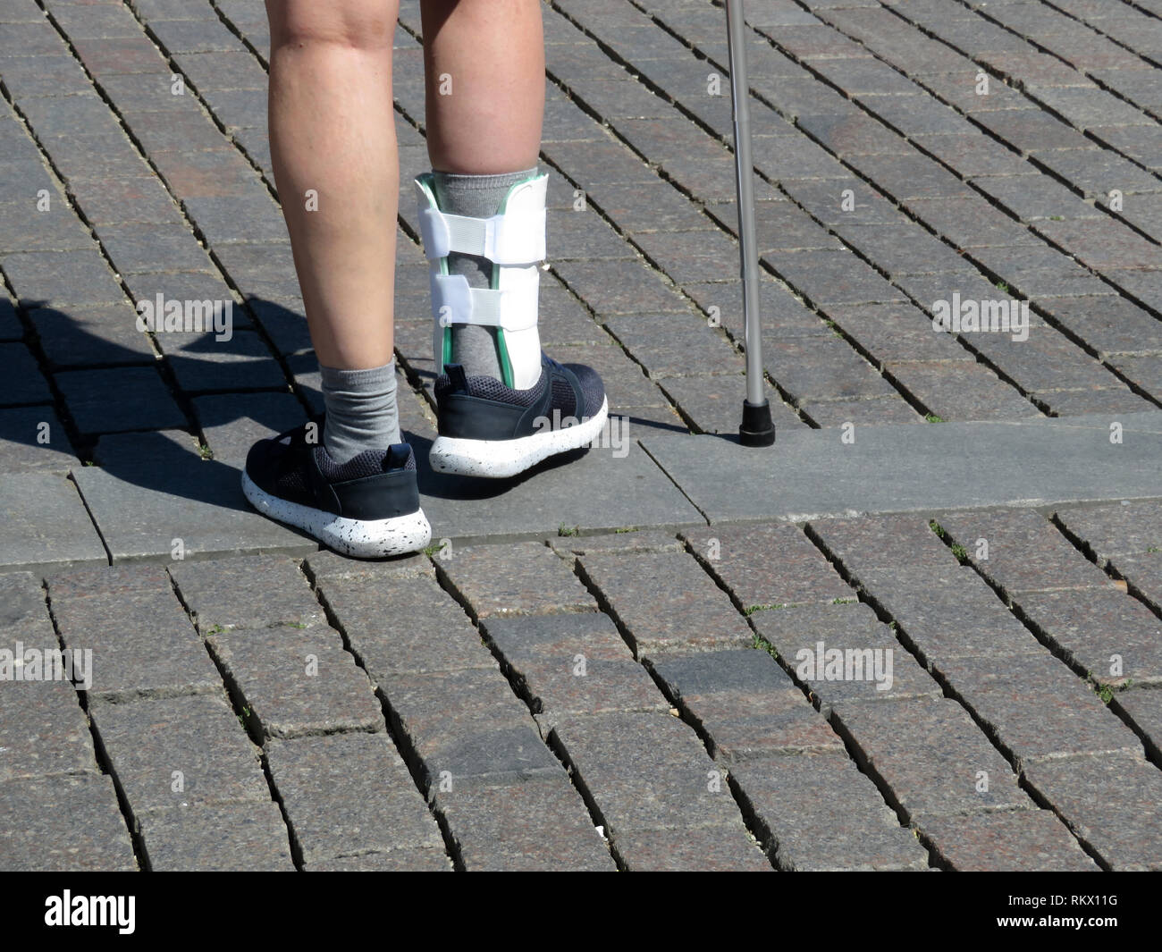 Female feet with the splint, orthosis for leg. Person with cane walking after a broken or sprain legs. Orthopedic orthosis for immobilizing foot - Stock Image