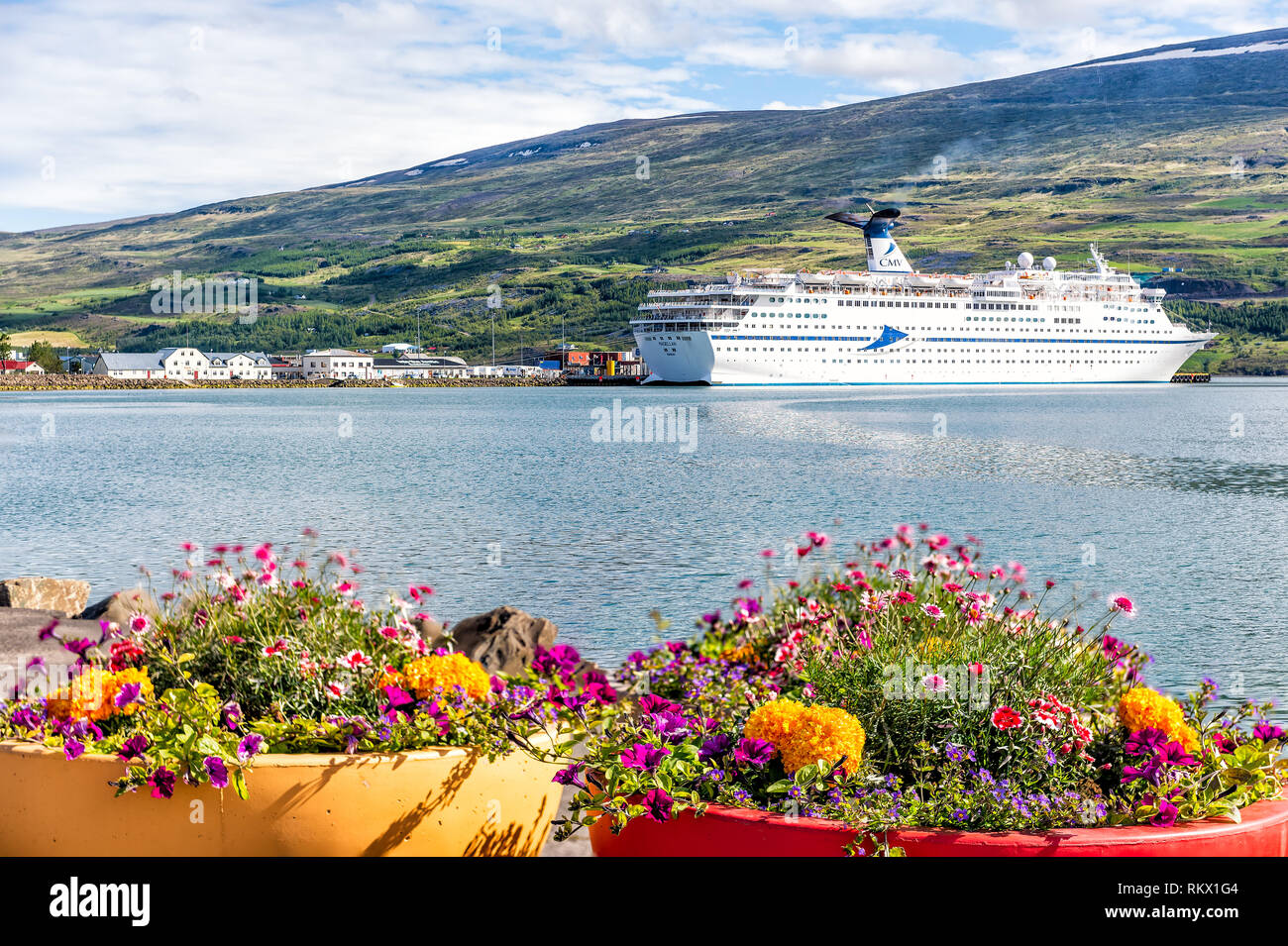 Akureyri, Iceland - June 17, 2018: Fishing village town harbor marina with cruise ship boat and fjord with mountains and flower pots - Stock Image