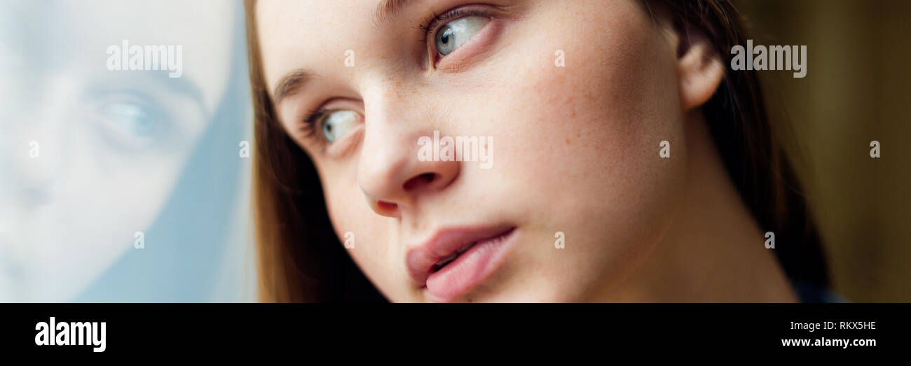 Young depressed lonely female college student standing by a window at her school, looking out. Education, Bullying, Depression, Despair and Emotional  - Stock Image