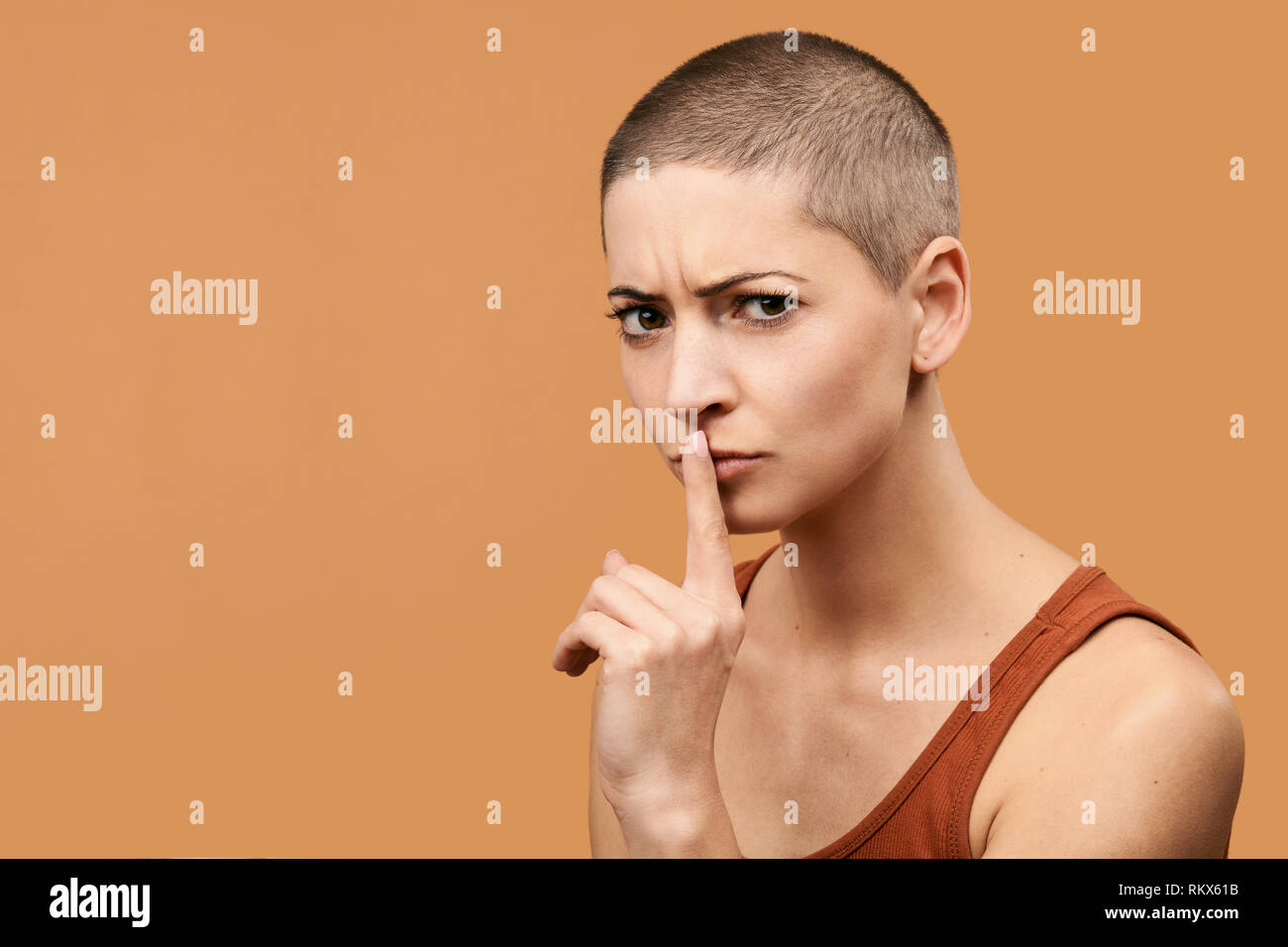 Attractive mid 30s woman pressing finger to lips as if asking to keep silent. Photo of young angry woman making Shhh gesture. - Stock Image
