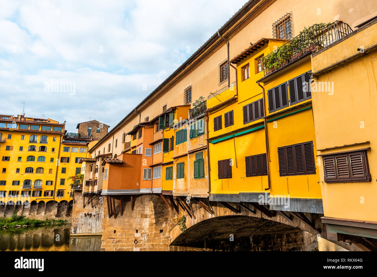 Florence, Italy Firenze orange yellow colorful building closeup on Ponte Vecchio by Arno river during summer morning in Tuscany with nobody vibrant - Stock Image