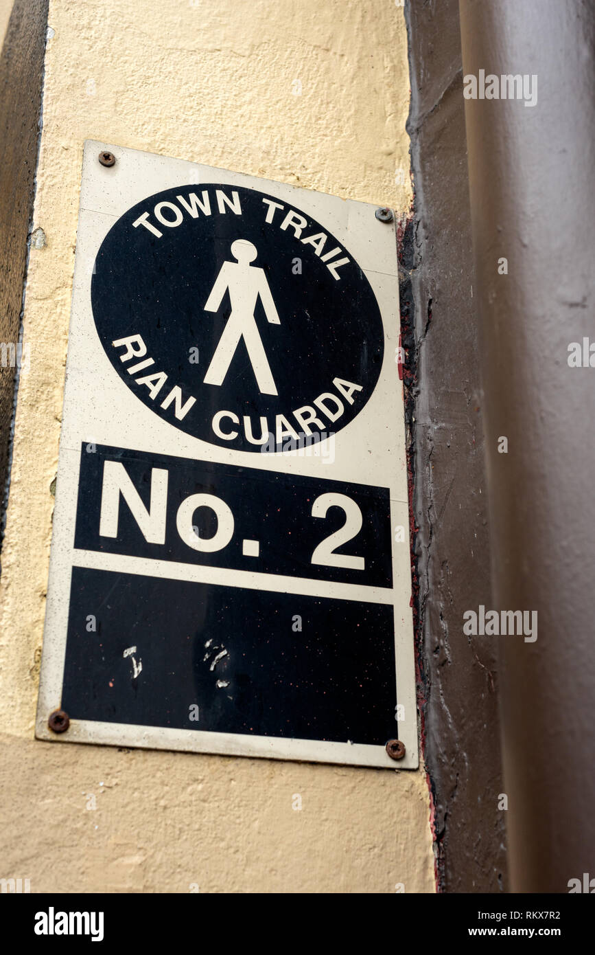 Town trail sign in both English and Irish. Dated old fashioned wall trail guide sign information notice. - Stock Image