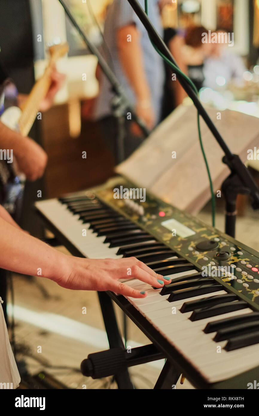 shot of female hands playing the piano. Hands of man playing the piano at a party. girl playing the synthesizer keyboard - Stock Image