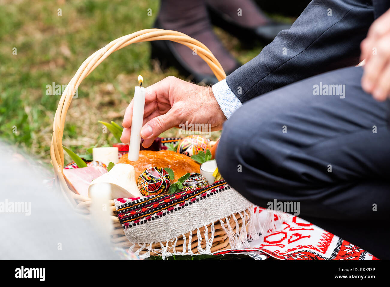 Ukrainian Orthodox Easter Blessing Wicker Straw Baskets With Senior Man Hand Placing Candle On Grass Ground Outside At Church With Flame Stock Photo Alamy