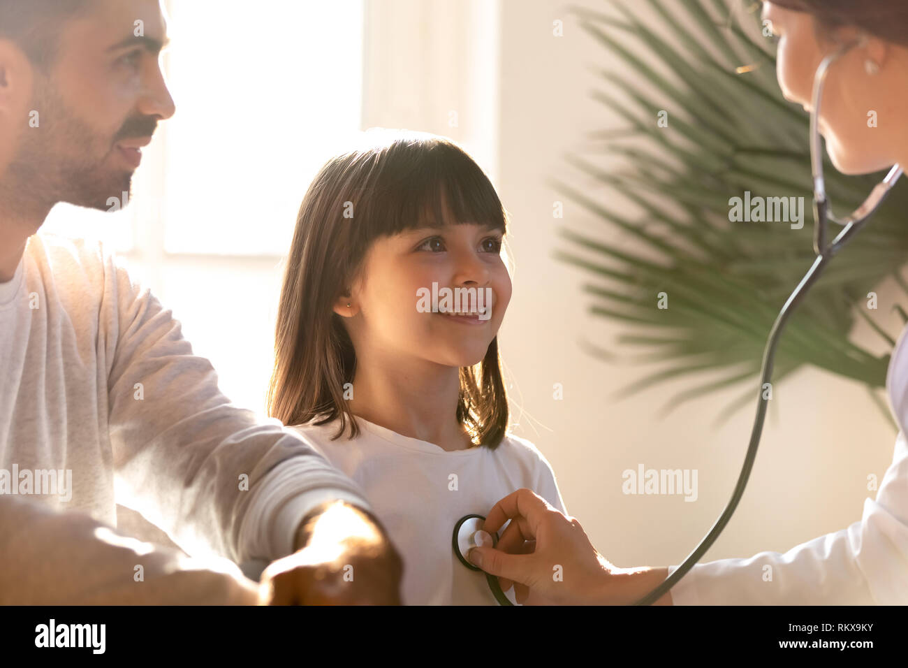 Female pediatrician holding stethoscope examining child visiting doctor with father - Stock Image