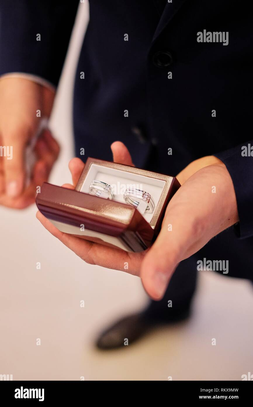 Man's hands holding a white box with wedding rings - Stock Image