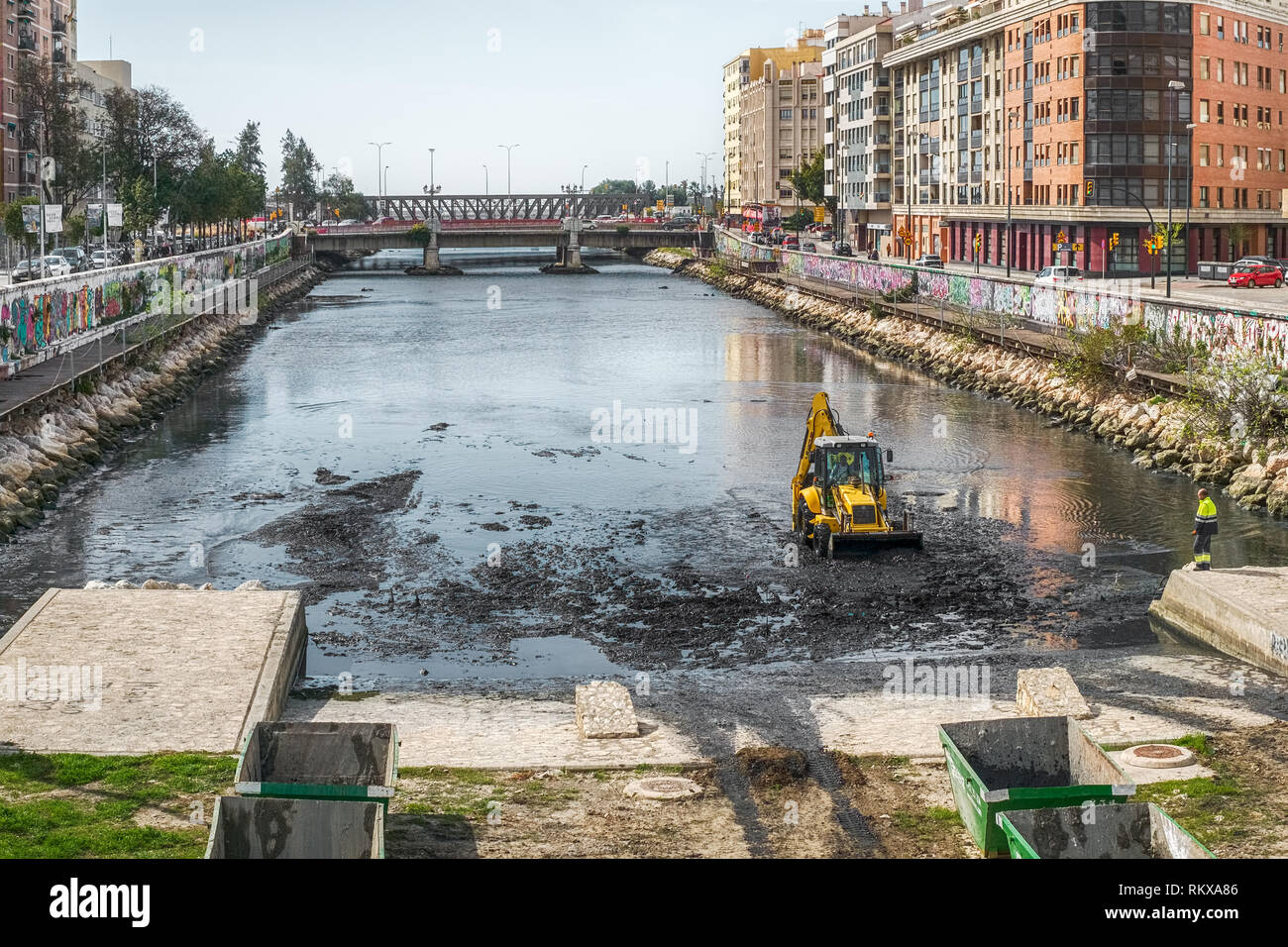 Malaga, Spain - March 23, 2018. Front end loader cleans dirty sewage rubbish in Guadalmedina river, Malaga city, Costa del sol, Spain - Stock Image