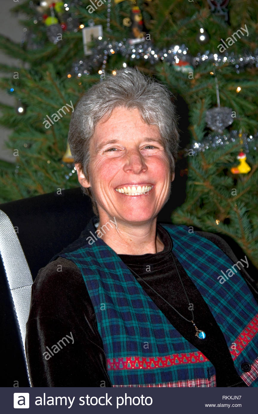 woman; portrait; attractive, wide smile; greying hair; Christmas tree; happy; holiday, celebration, vertical; MR - Stock Image
