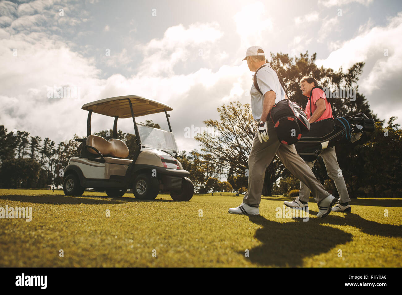 Senior golfers walking together in the golf course with their golf bags. Senior golfers walking and talking after the game. - Stock Image