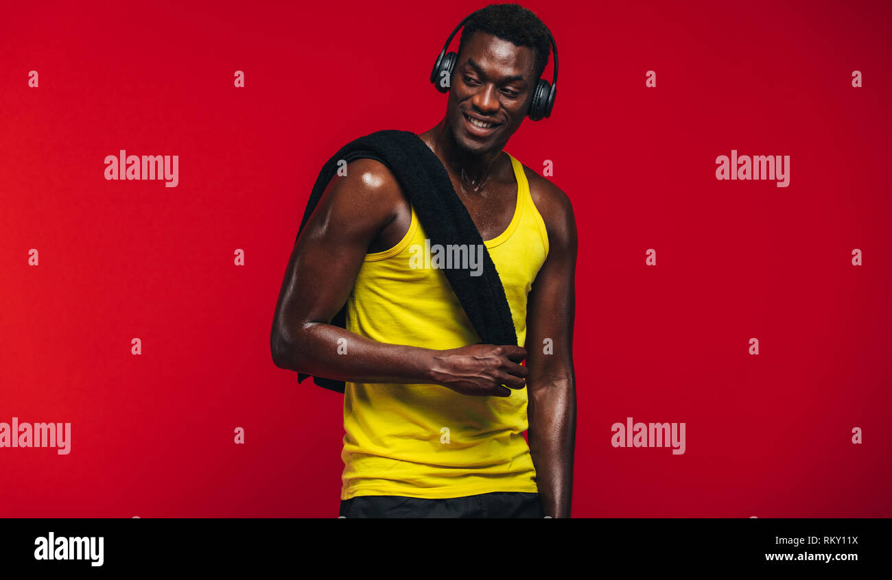 Fitness man with towel on shoulder listening to music on headphones. Fit young man resting after from workout on red background. - Stock Image