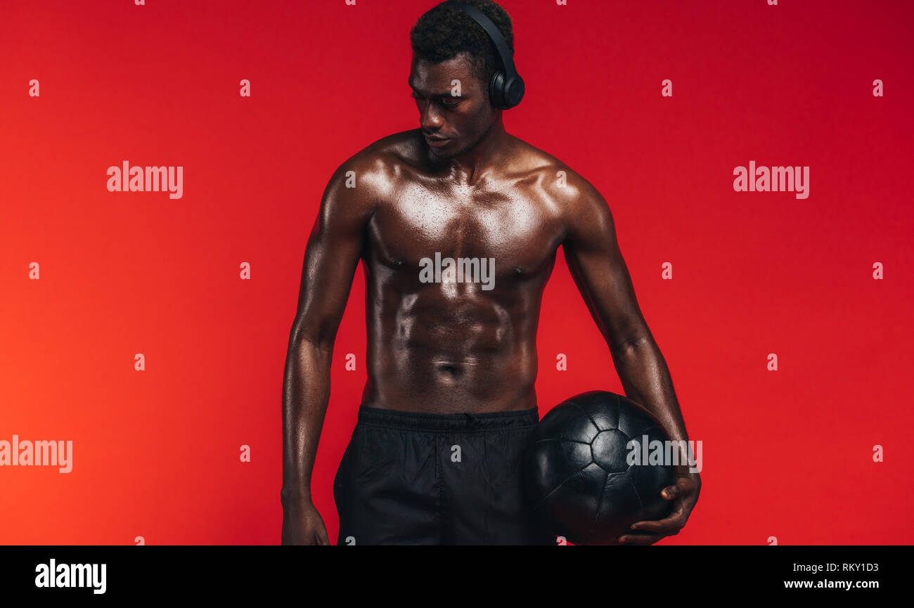 Fit young man with medicine ball standing against red background. African american male model with muscular body wearing headphones and holding a fitn - Stock Image