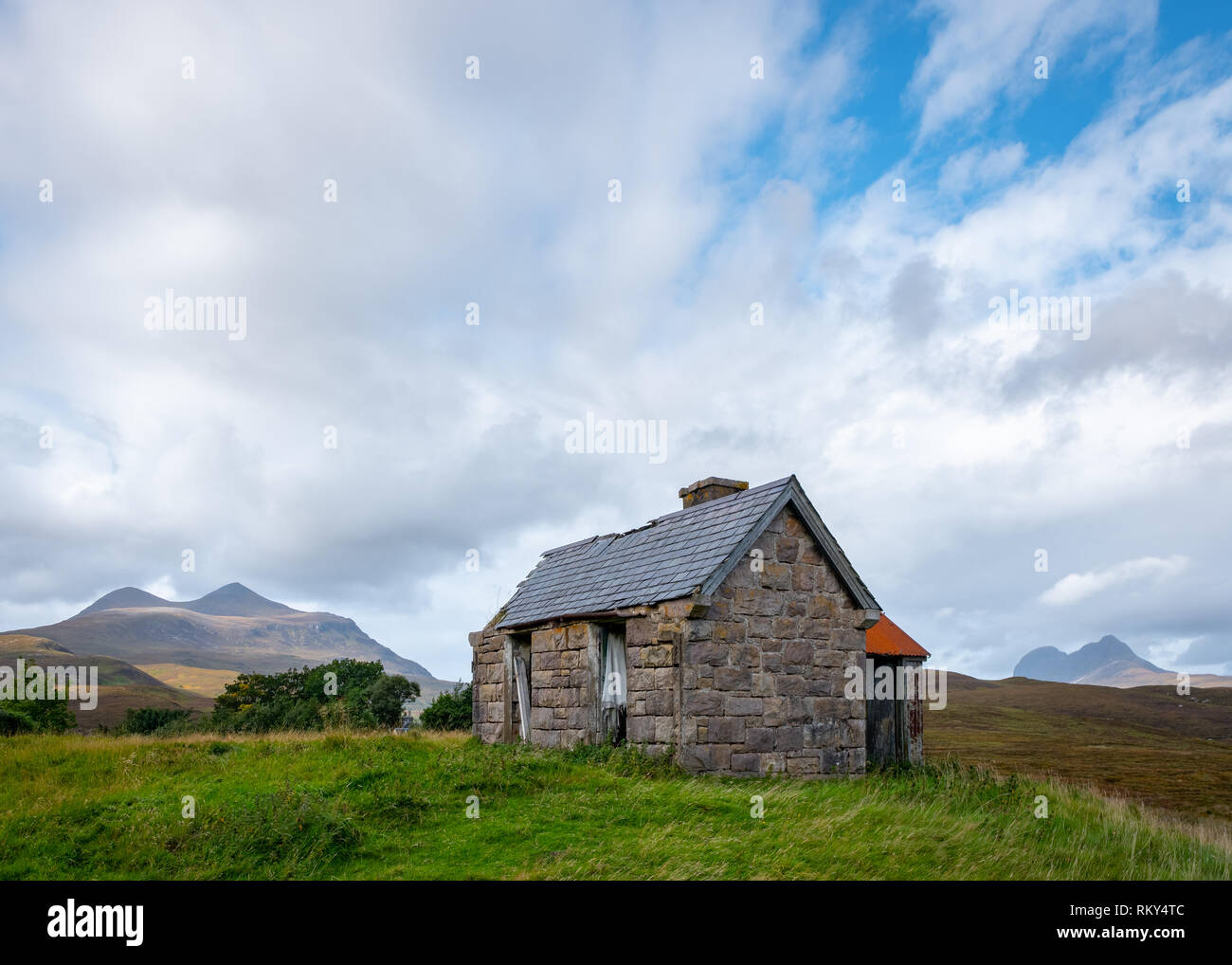 An abandoned crofters cottage, now used as a shelter for sheep, with mountains Cul Mor and Suilven in the background, Elphin, Sutherland, Scotland - Stock Image