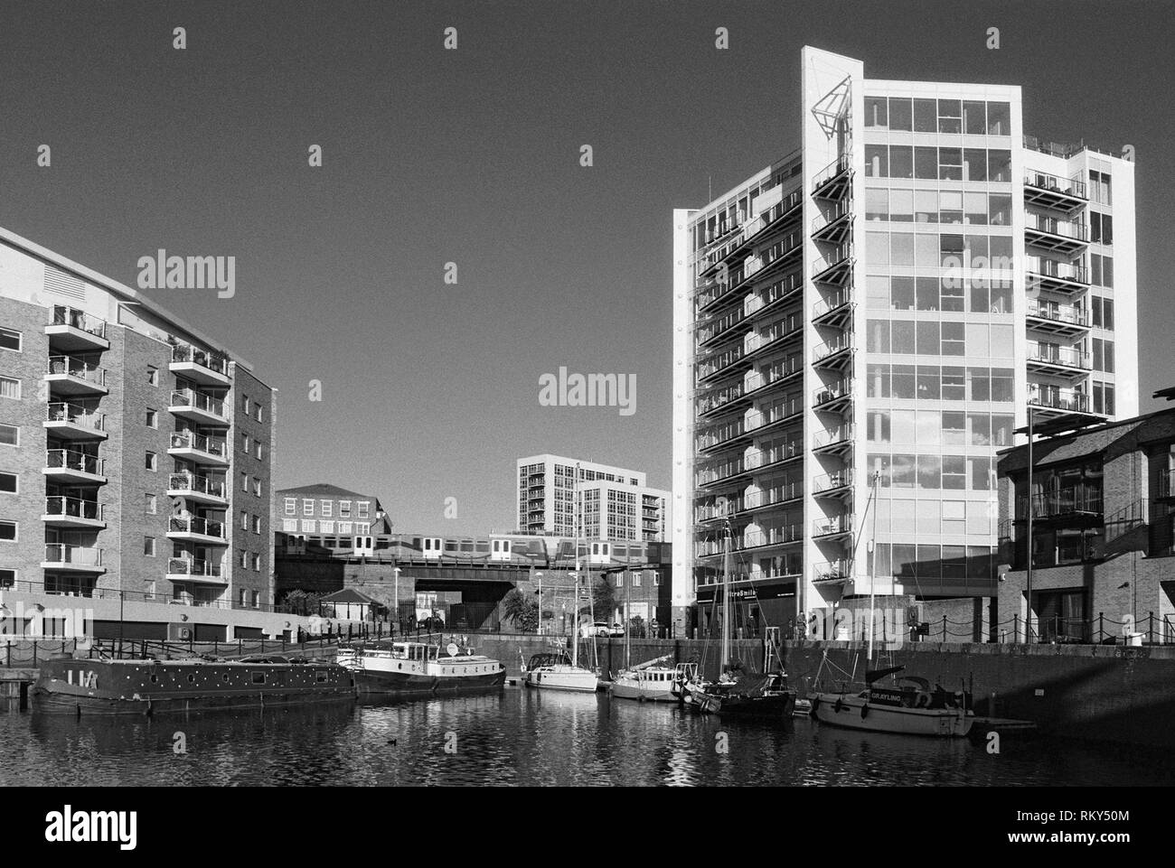 Limehouse Basin in London's Docklands district, UK, with boats and the Docklands Light Railway - Stock Image