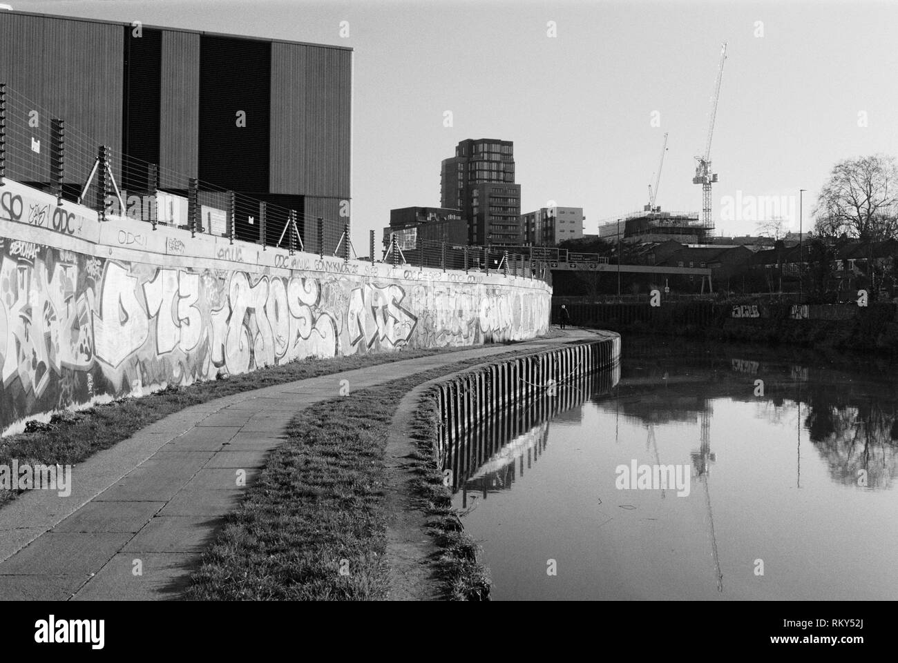 Wall with graffiti and footpath along the River Lea near Bromley-By-Bow, East London, UK, with modern buildings in background - Stock Image