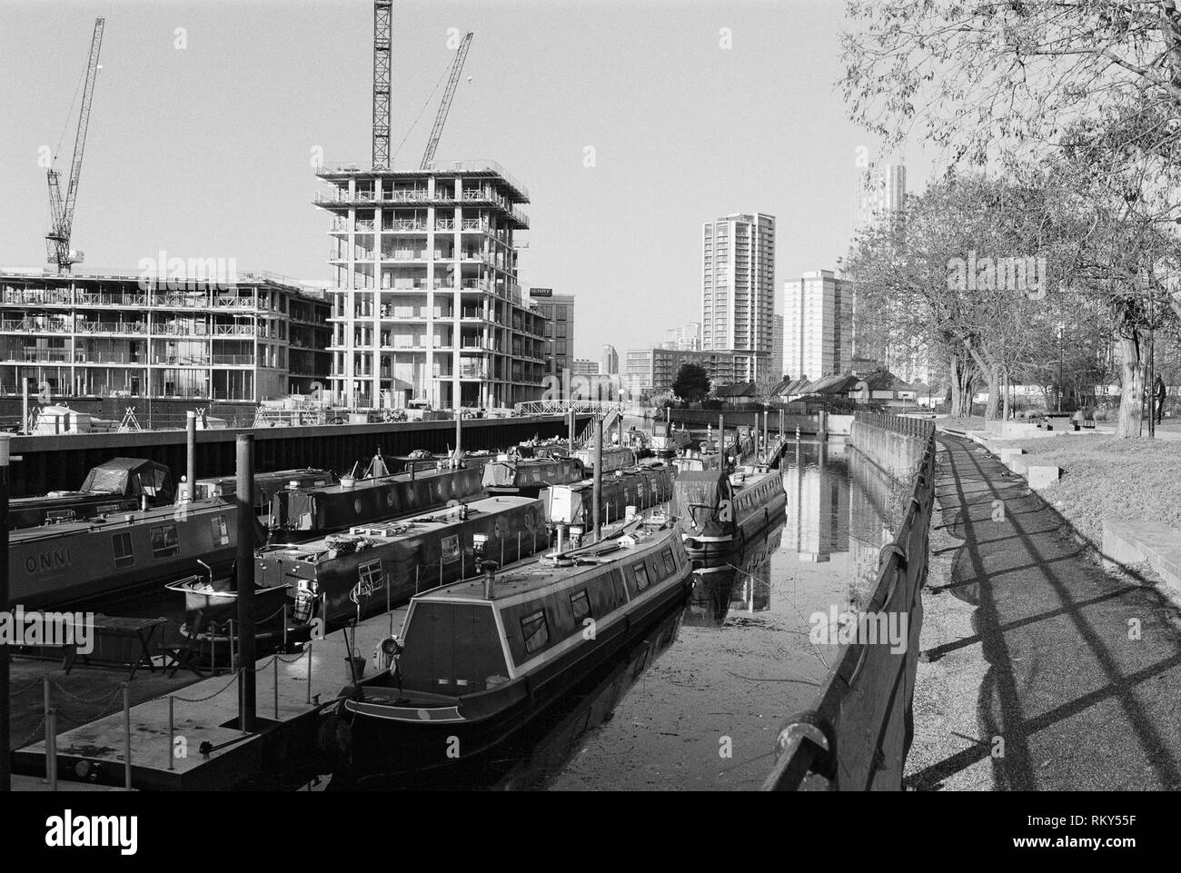 Narrowboats moored on Three Mills Wall River, Bromley-By-Bow, East London UK, looking towards Stratford, with new apartments under construction - Stock Image