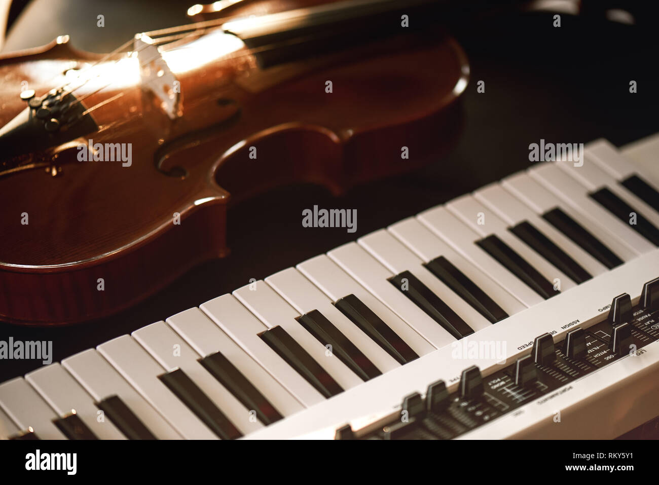 Listening classical music. Close-up view of classical violin instrument lying on a synthesizer. Music concept. Musical instruments. - Stock Image
