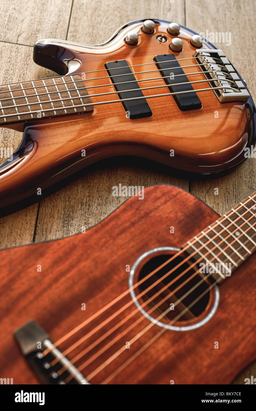 Choosing a guitar...Top view on two perfect polished musical instruments: acoustic and electric guitars are lying on the wooden floor in a music shop. Musical instruments. Music concept. Guitar body - Stock Image