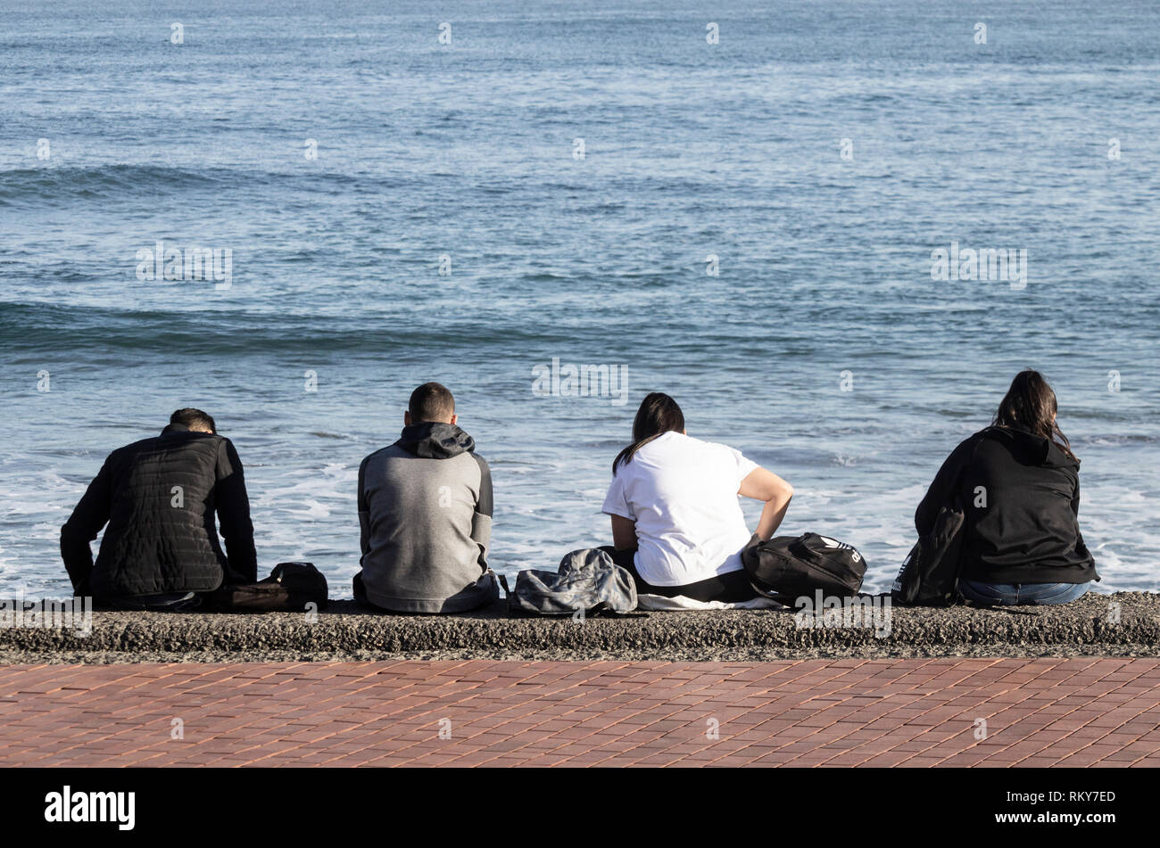 Rear view of four teenagers sitting on sea wall and looking at mobile phones: boredom, bored teenager, social media... concept. - Stock Image