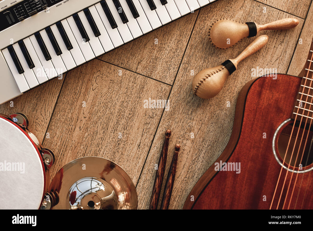 Creating a melody...Top view of musical instruments set: synthesizer, electronic guitar, wooden drum sticks, golden cymbal, drums, gold maracas and tambourine lying on wooden background. Musical instruments. Music equipment - Stock Image