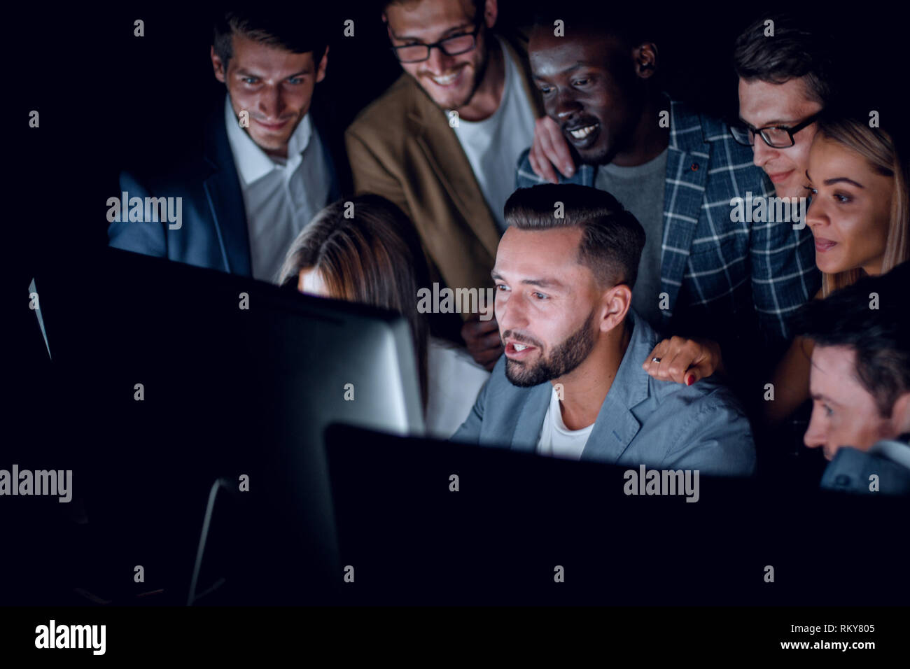 business team looks closely at the screens of computer monitors - Stock Image