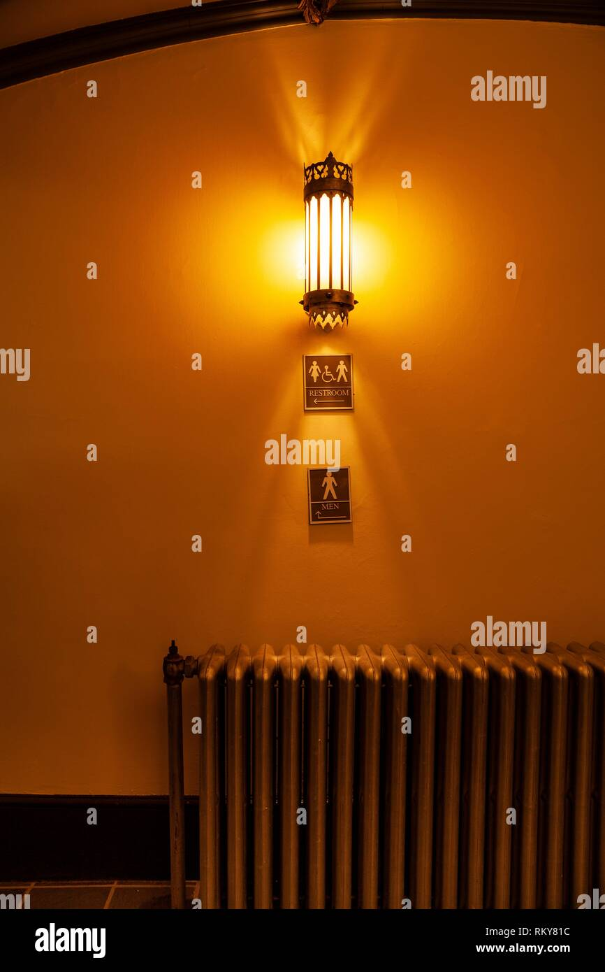 Light fixture on a wall with old cast iron radiator and signs reading '' Restroom'' and ''Men'' below it. - Stock Image