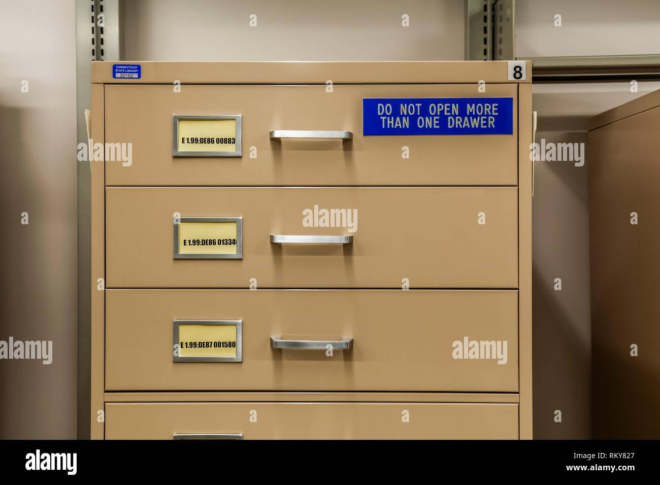 Filing cabinet, with sign reading ´Do Not Open More Than One Drawer´ in a library. - Stock Image