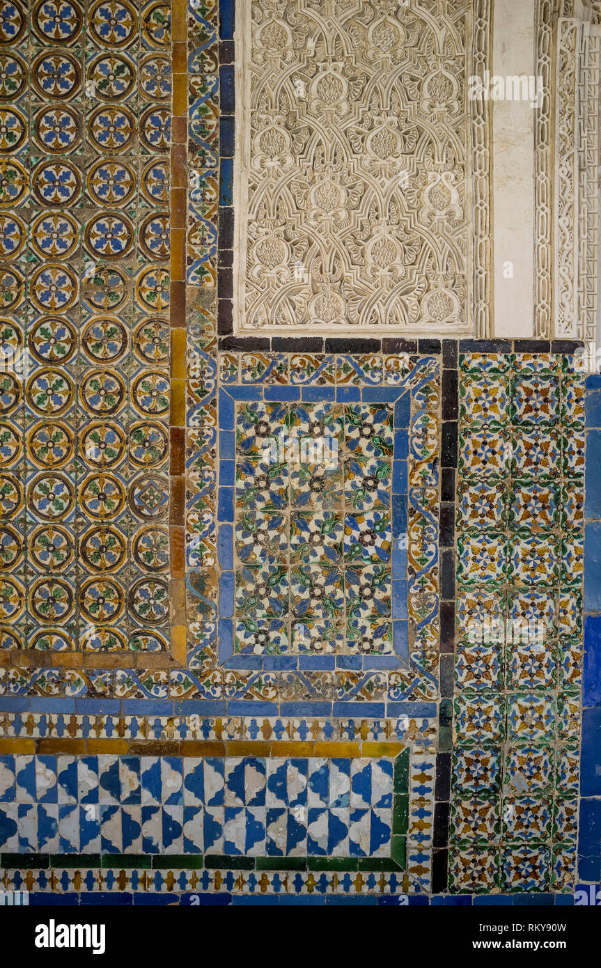 A view of colourful Mudejar interior wall tiles and stone fretwork in the Real Alcazar, Seville, Spain - Stock Image