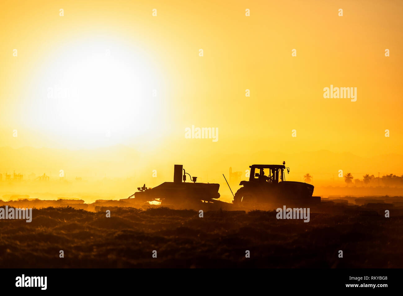 Wide shot of tractor silhouette farming at sunrise. Stock Photo