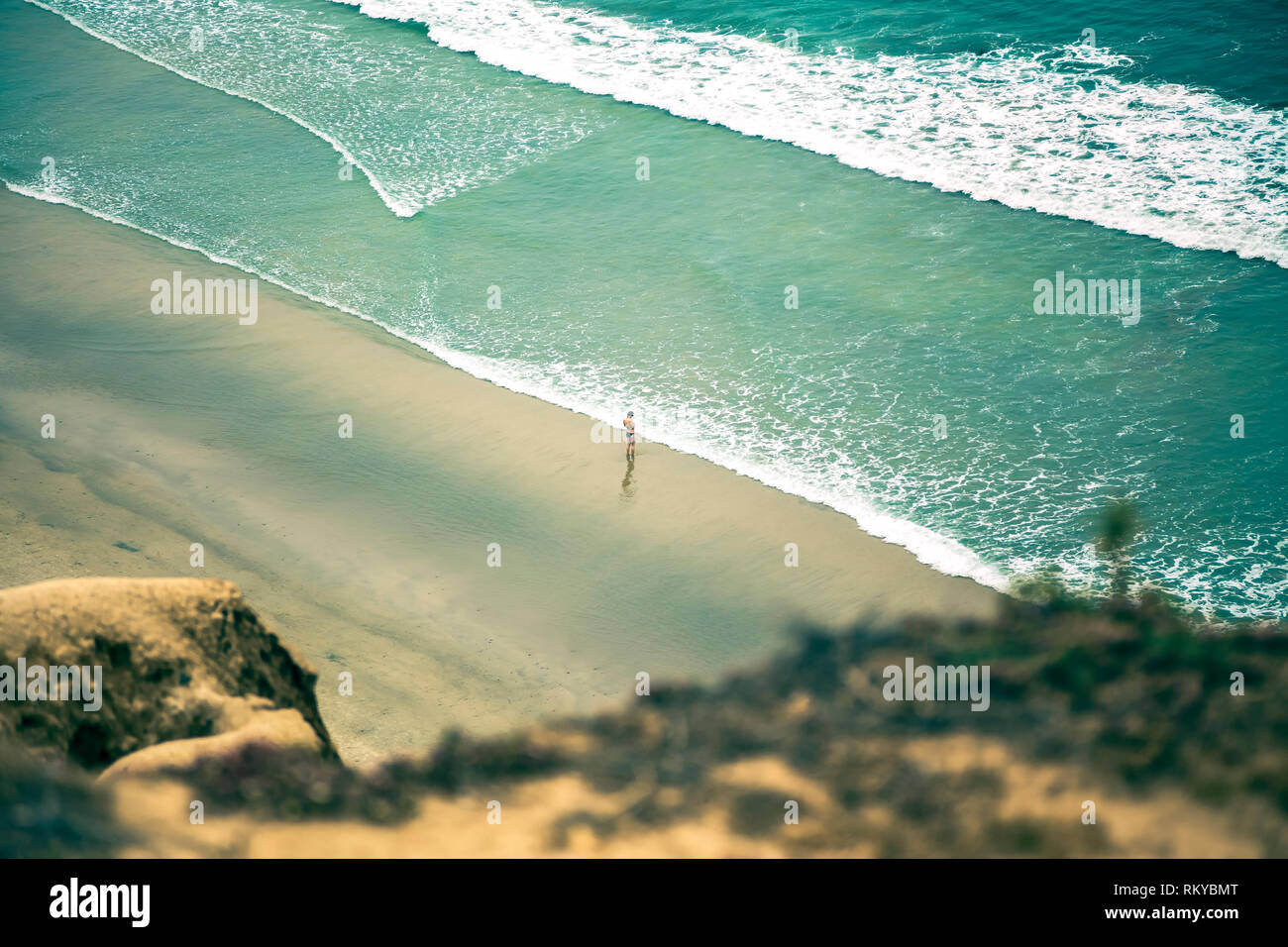 Overhead of girl in bathing suit standing on the beach alone at the edge of the ocean. - Stock Image