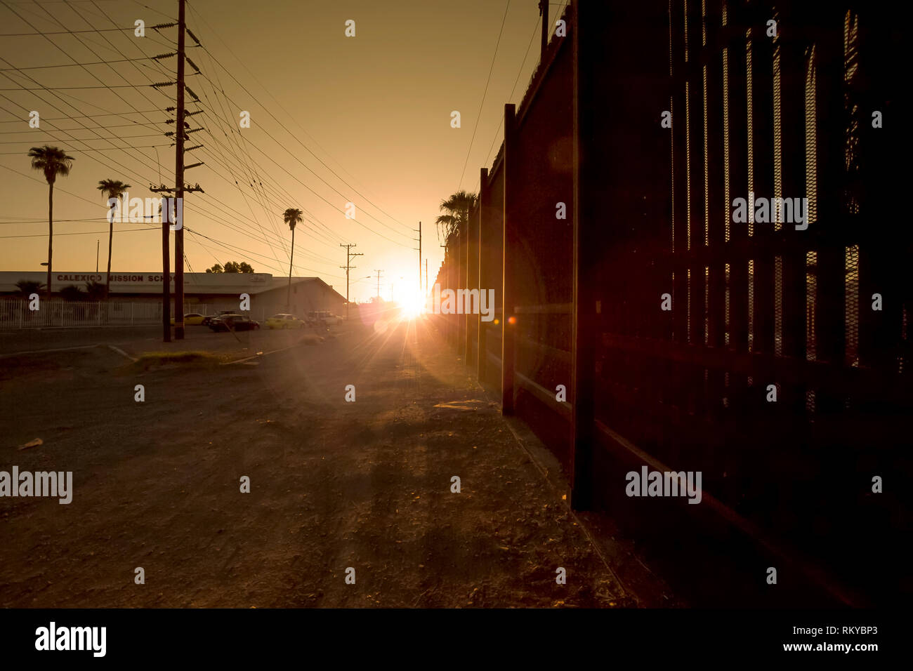 Sunrise along the border fence separating the United States and Mexico. - Stock Image