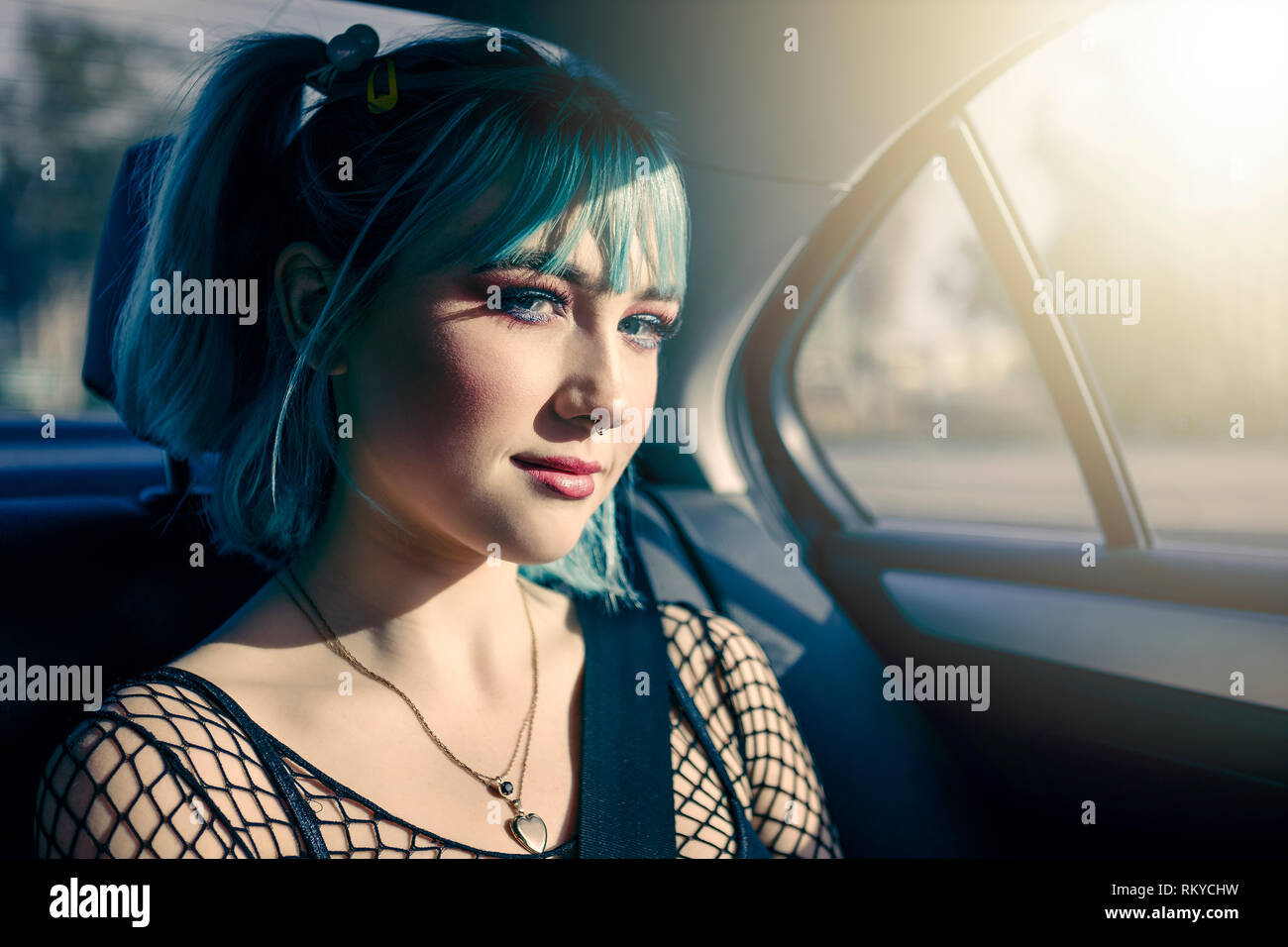 Portrait of teen girl with blue hair and pierced nose in the backseat of a car while on a roadtrip. Stock Photo