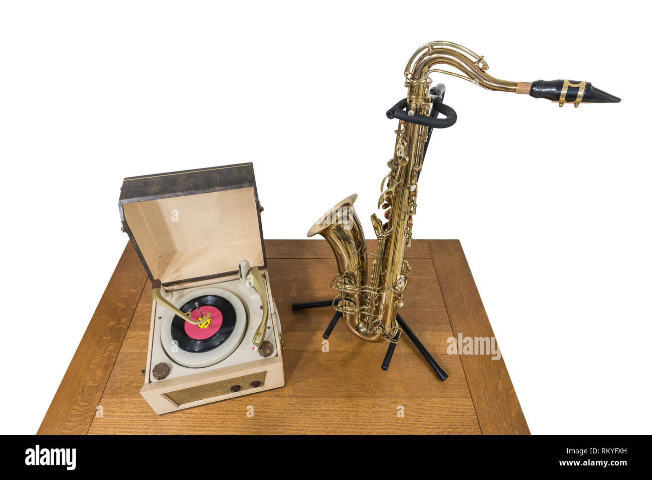 Vintage record player and saxophone on wood table isolated on white. Stock Photo