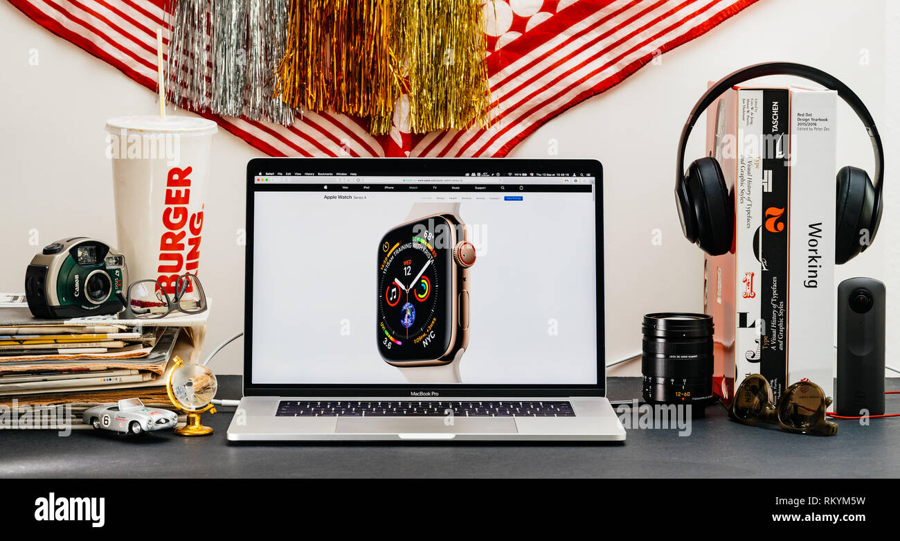 LONDON, UK - SEP 13, 2018: Creative room table with Safari Browser on MacBook Pro laptop showcasing Apple Computers website latest Apple Watch series 4 presentation on screen with complications and face - Stock Image
