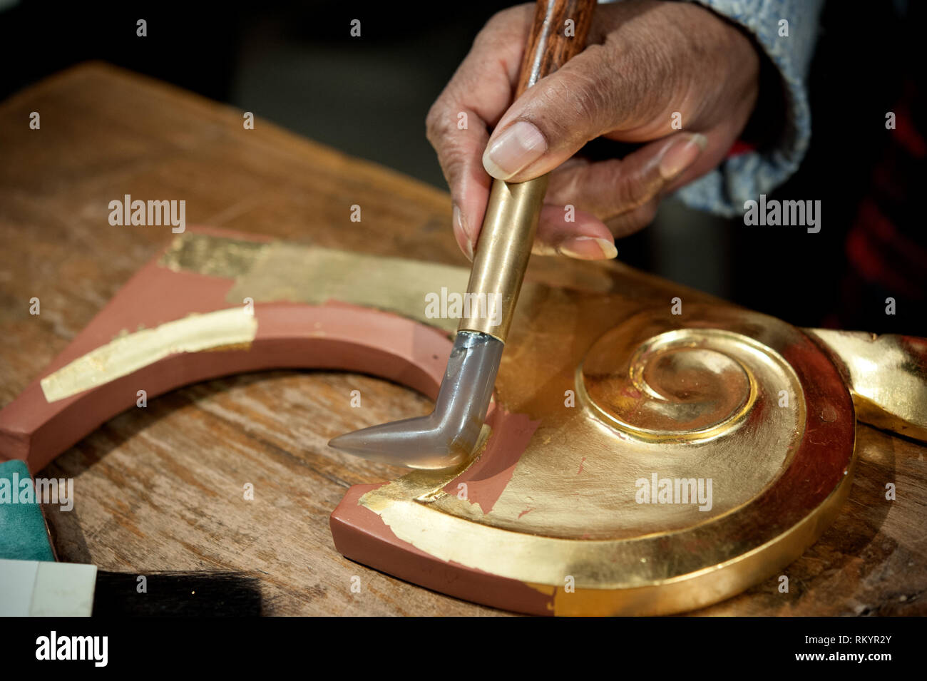 Craftsman uses agate stone for the burnish process. Gilding tecnique. - Stock Image
