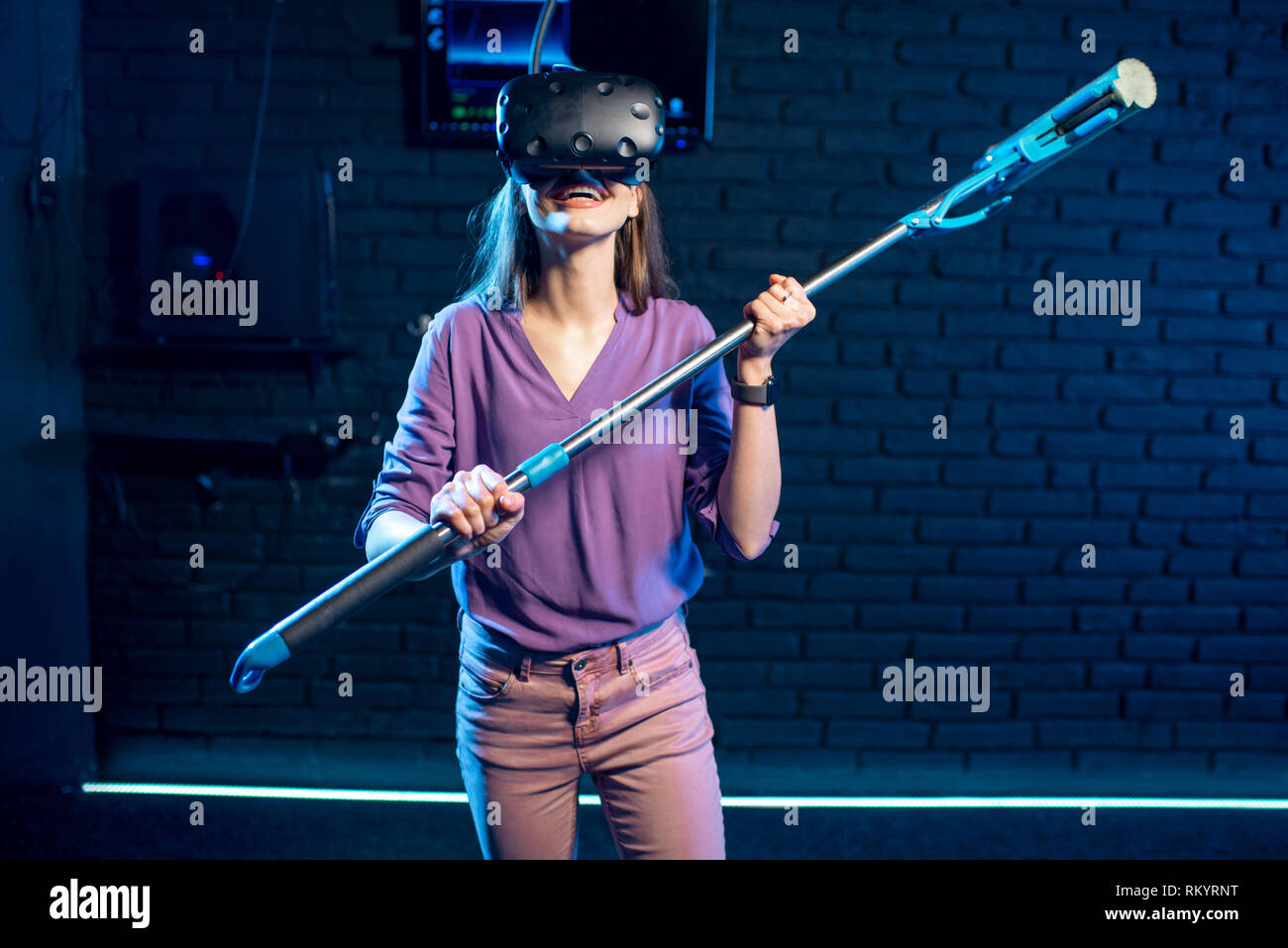 Woman in virtual reality imagines herself as a housewife standing with washing swab indoors - Stock Image